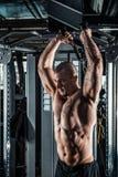 Uomo muscolare durante l'allenamento nella palestra Fotografia Stock