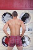 Uomo muscolare in lavanderia automatica immagini stock