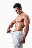 Uomo muscolare in pantaloni graduati eccessivi Fotografie Stock Libere da Diritti