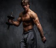 Uomo muscolare senza camicia che fa allenamento del bicipite Fotografie Stock