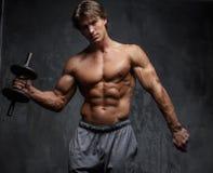 Uomo muscolare senza camicia che fa allenamento del bicipite Fotografie Stock Libere da Diritti