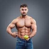 Uomo muscolare senza camicia che indica la mela fresca Fotografia Stock Libera da Diritti
