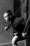 Uomo muscolare sicuro che fa un esercizio fisico Immagini Stock Libere da Diritti