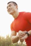 Uomo muscolare sorridente dei giovani che controlla il suo tempo sul suo orologio in un parco a Pechino Immagini Stock
