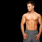 Uomo muscolare sportivo ed in buona salute isolato sul nero Immagine Stock Libera da Diritti
