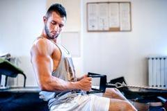 Uomo muscolare sull'allenamento quotidiano alla palestra Concetto di forma fisica Immagine Stock