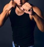 Uomo muscolare in una posizione di inscatolamento Fotografie Stock