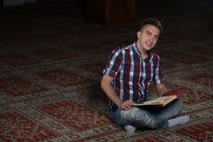 Uomo musulmano che legge il Corano islamico santo del libro Fotografie Stock