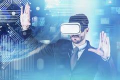 Uomo negli impianti della cuffia avricolare di VR con il flusso continuo della tecnologia immagini stock