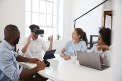 Uomo negli occhiali di protezione di VR ad uno scrittorio guardato dai colleghi in ufficio fotografia stock libera da diritti