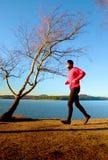 Uomo nei funzionamenti rosa del rivestimento alla linea costiera Sport e allenamento di addestramento di stile di vita del paese  Immagini Stock Libere da Diritti