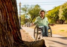 Uomo nei gesti della sedia a rotelle all'ostacolo del marciapiede Fotografie Stock