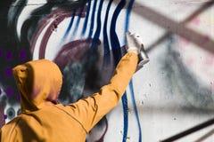 Uomo nei graffiti della vernice del cappuccio fotografie stock libere da diritti