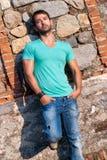 Uomo nei supporti dell'abbigliamento casual contro una parete della roccia del mattone Fotografie Stock