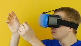 Uomo nei tocchi della cuffia avricolare del vr dalla sua realtà virtuale delle mani, esposizione testa-montata stock footage