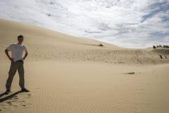 Uomo nel bianco alle dune di sabbia Immagine Stock