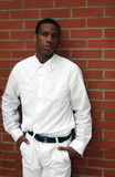 Uomo nel bianco dal muro di mattoni fotografia stock