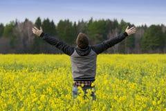 Uomo nel campo con i fiori gialli Fotografia Stock