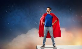 Uomo nel capo rosso del supereroe sopra cielo notturno fotografie stock