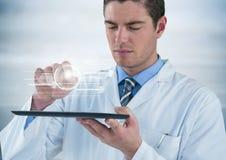 Uomo nel cappotto del laboratorio con la compressa e nell'interfaccia bianca con il chiarore contro fondo grigio Immagini Stock Libere da Diritti