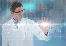 Uomo nel cappotto e negli occhiali di protezione del laboratorio con il grafico bianco e chiarore contro fondo blu con bokeh fotografia stock libera da diritti