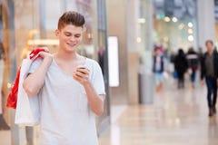 Uomo nel centro commerciale facendo uso del telefono cellulare Fotografia Stock Libera da Diritti