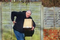 Uomo nel dolore che porta scatola pesante Parte posteriore di Male fotografia stock libera da diritti