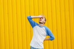Uomo nel dolore che tocca il suo capo su un fondo giallo Concetto di emicrania Copi lo spazio Immagini Stock