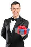 Uomo nel legame di arco e del vestito che dà un regalo Immagine Stock
