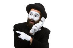 Uomo nel mimo di immagine che tiene un microtelefono fotografia stock