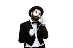 Uomo nel mimo di immagine che tiene un microtelefono immagini stock