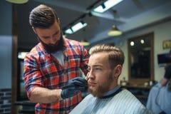 Uomo nel negozio di barbiere fotografie stock