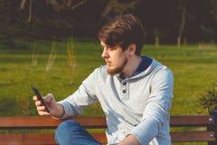 Uomo nel parco con un telefono in mani Fotografie Stock Libere da Diritti