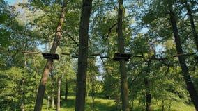 Uomo nel parco della corda di avventura che fa gli esercizi rampicanti sul fascio di equilibrio di estate video d archivio