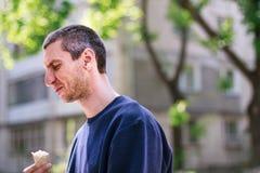 Uomo nel pulover blu che mangia gelato nel parco fotografie stock