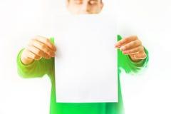 Uomo nel sorriso della maglietta felpata della pianta, mano che tiene A4 aletta di filatoio in bianco, D Fotografie Stock Libere da Diritti
