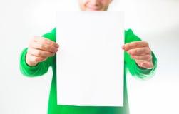 Uomo nel sorriso della maglietta felpata della pianta, mano che tiene A4 aletta di filatoio in bianco, D Fotografia Stock