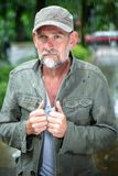 Uomo nel suo 50s che cammina all'aperto nella pioggia Immagini Stock Libere da Diritti
