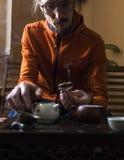 Uomo nel tè squisito di miscela in teiera a cerimonia di tè del cinese tradizionale Insieme di attrezzatura fotografie stock libere da diritti