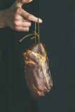 Uomo nel taglio nero della tenuta dell'abbigliamento di carne di maiale curata Fotografia Stock