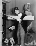 Uomo nell'abbigliamento convenzionale ed in un cane che prova a suonare la campana con il suo bastone da passeggio (tutte le pers Immagini Stock