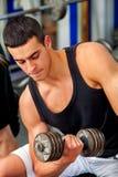 Uomo nell'allenamento della palestra con l'attrezzatura di forma fisica Fotografia Stock