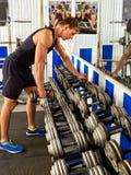 Uomo nell'allenamento della palestra con l'attrezzatura di forma fisica Colpo potato Fotografia Stock