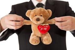 Uomo nell'orso di orsacchiotto della holding del vestito Immagini Stock