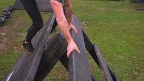 Uomo nell'ostacolo rampicante della piramide di corsa ad ostacoli video d archivio