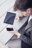 Uomo nell'ufficio facendo uso dello smartphone Fotografia Stock Libera da Diritti