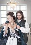 Uomo nella bella donna della copertura medievale del costume dal suo cappotto Fotografia Stock