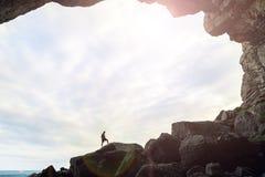 Uomo nella caverna con un fondo del cielo fotografia stock libera da diritti