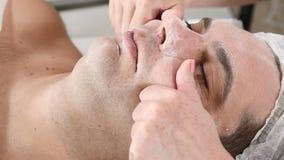 Uomo nella clinica di bellezza Il cliente maschio ottiene la procedura facciale di cosmetologia nel salone di bellezza Massaggio  archivi video