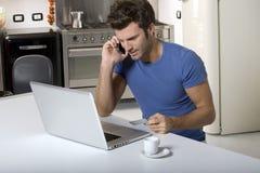 Uomo nella cucina con il computer portatile Fotografia Stock